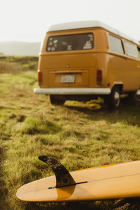 Yellow surfboard and vintage recreational van on roadside, Exeter, California, USAの写真素材 [FYI03594690]