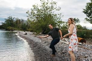 Couple skimming stones on beach, Oshawa, Canadaの写真素材 [FYI03594730]