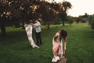 Young couple preparing picnic blanket and pink champagne in park at duskの写真素材 [FYI03594741]