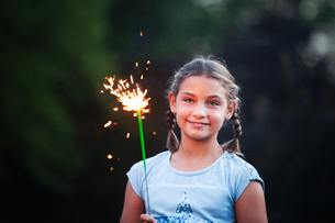 Portrait of girl holding sparkler in garden at dusk on independence day, USAの写真素材 [FYI03594765]
