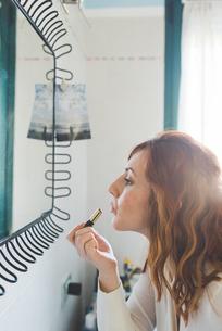 Young woman applying lipstick at bathroom mirrorの写真素材 [FYI03594996]
