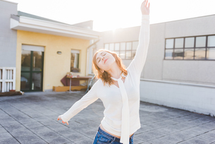 Beautiful young woman dancing on sunlit roof terrace with eyes closedの写真素材 [FYI03595010]