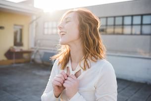 Young woman with red hair laughing on sunlit roof terraceの写真素材 [FYI03595014]