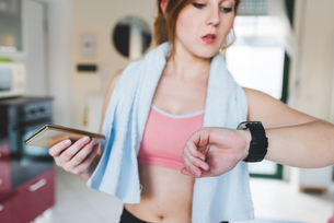 Young woman training, looking at smartwatchの写真素材 [FYI03595029]