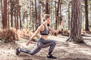 Young woman in forest, exercising, doing lungesの写真素材 [FYI03595038]