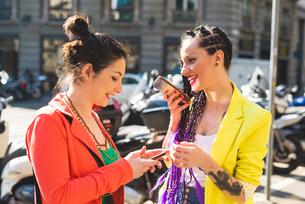 Women in city break using mobile phone, Milan, Italyの写真素材 [FYI03595175]