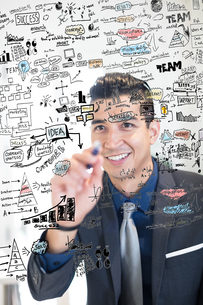 Young businessman writing ideas on glass wall in creative officeの写真素材 [FYI03595259]