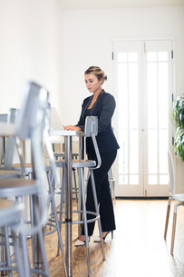 Young businesswoman typing on laptop in creative officeの写真素材 [FYI03595260]
