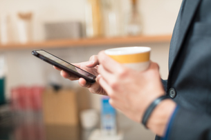 Hands of businessman holding coffee cup and smartphoneの写真素材 [FYI03595274]