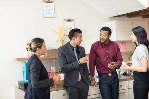 Businesswomen and men having informal meeting in office kitchenの写真素材 [FYI03595277]