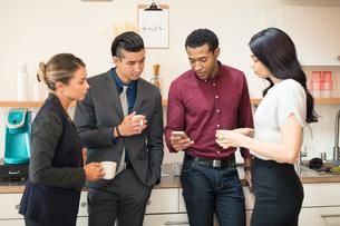 Businesswomen and men looking at smartphone in office kitchenの写真素材 [FYI03595279]
