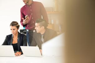 Businesswoman and men having meeting at office deskの写真素材 [FYI03595280]