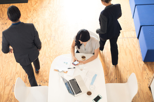 Overhead view of young businesswoman looking at smartphone at office tableの写真素材 [FYI03595281]