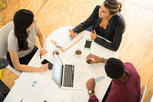 Overhead view of three businesswomen and men meeting at office tableの写真素材 [FYI03595282]