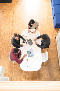 Overhead view of four businesswomen and men meeting at office tableの写真素材 [FYI03595283]