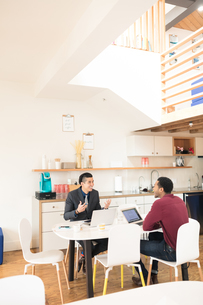 Young businessman explaining to colleague at office tableの写真素材 [FYI03595284]