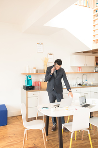 Young businessman making smartphone call at office tableの写真素材 [FYI03595286]