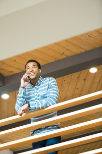 Young businessman on balcony making smartphone callの写真素材 [FYI03595295]