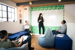 Young businesswoman giving whiteboard presentation in creative meeting roomの写真素材 [FYI03595312]