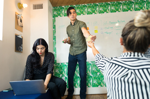 Young businessman handing out adhesive notes in creative meeting roomの写真素材 [FYI03595317]