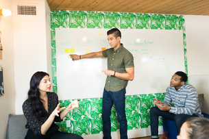 Young businessman pointing at whiteboard in creative meeting roomの写真素材 [FYI03595319]