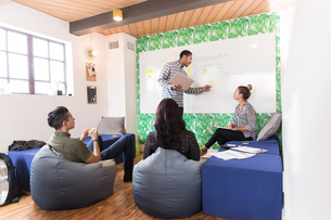Young businessman pointing at whiteboard in creative meeting roomの写真素材 [FYI03595329]