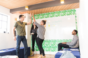 Young businessmen and women high fiving in creative meeting roomの写真素材 [FYI03595332]
