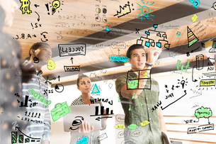 Young businesswoman drawing diagrams on glass wall in creative officeの写真素材 [FYI03595333]