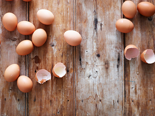 Eggs and egg shells on wooden surface, overhead viewの写真素材 [FYI03595365]