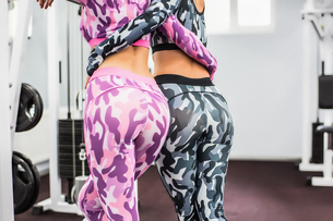 Rear view of friends in gym wearing lycra, arms around each otherの写真素材 [FYI03595431]
