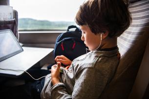 Young boy travelling on train, using digital tablet, wearing earphonesの写真素材 [FYI03595454]