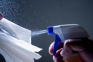 Cropped view of man spraying cleaning product of clothの写真素材 [FYI03595527]