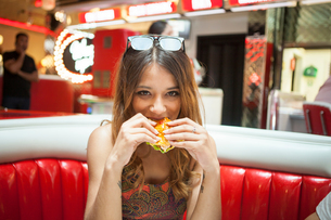 Portrait of young woman sitting in diner, eating sandwichの写真素材 [FYI03595652]