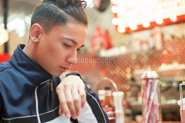 Young man sitting in diner, talking into smartwatchの写真素材 [FYI03595663]