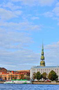 ラトビア・首都リガのダウガヴァ川を巡る観光船から見た聖ペトロ教会の尖塔や船が停泊する景観の写真素材 [FYI03595727]