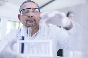 Laboratory worker taking test tube from rackの写真素材 [FYI03595789]