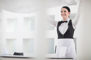 Waitress in restaurant laying table clothの写真素材 [FYI03595839]