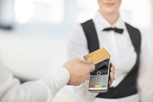Waitress holding payment machine toward customer, customer paying by contactless methodの写真素材 [FYI03595842]