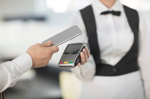 Waitress holding payment machine toward customer, customer paying by contactless methodの写真素材 [FYI03595844]