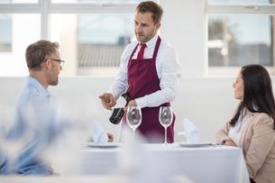 Waiter showing bottle of wine to diner in restaurantの写真素材 [FYI03595849]