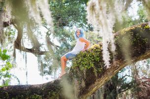 Girl sitting on old oak treeの写真素材 [FYI03595905]
