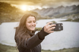 Teenage girl taking selfie in front of lake smiling, San Bernardino, Ticino, Switzerland, Europeの写真素材 [FYI03595927]