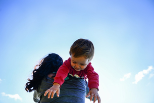 Low angle view of male toddler over mother's shoulder against blue skyの写真素材 [FYI03595968]