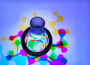 Laboratory flask containing a chemical formula with molecular structure background - illustrating reの写真素材 [FYI03595979]
