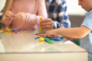 Father, son and daughter, sitting at table, playing with modelling clay, mid sectionの写真素材 [FYI03596144]
