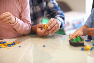 Father, son and daughter, sitting at table, playing with modelling clay, mid sectionの写真素材 [FYI03596147]