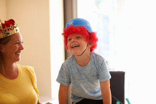 Mother and son playing dress up, wearing funny hats, laughingの写真素材 [FYI03596156]