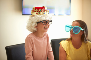 Mother and daughter playing dress up, wearing funny hats and glasses, laughingの写真素材 [FYI03596157]