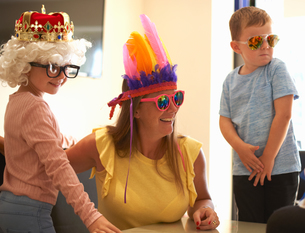 Mother, son and daughter playing dress up, wearing funny hats and glasses, laughingの写真素材 [FYI03596159]
