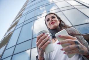 Businesswoman outside office building, holding coffee cup and smartphone, tattoos on hands, low anglの写真素材 [FYI03596165]